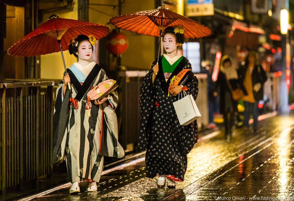 Geishas walking on the street with a red umbrella
