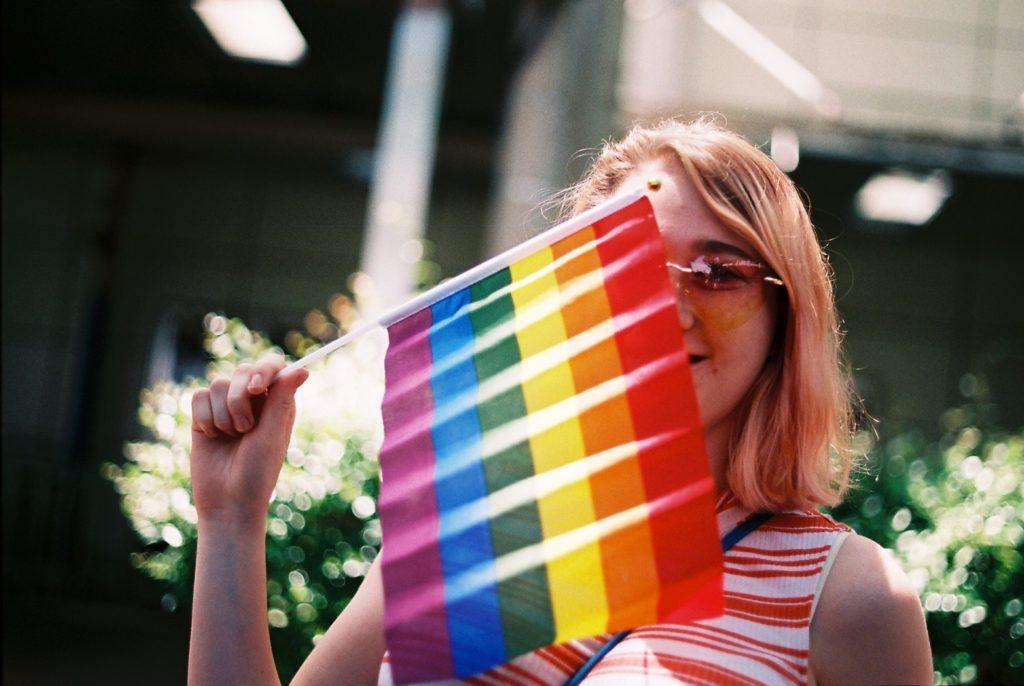 Frau hält eine LGBT Flagge