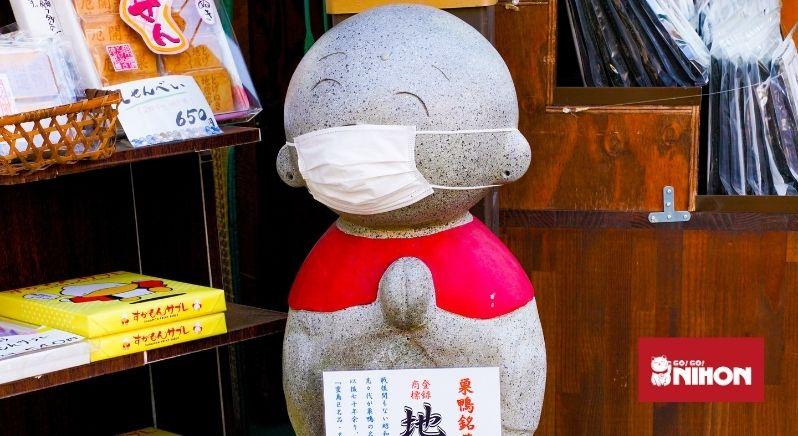 statue de pierre portant un masque