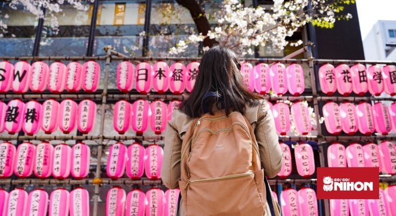 student with backpack in front of pink lanterns